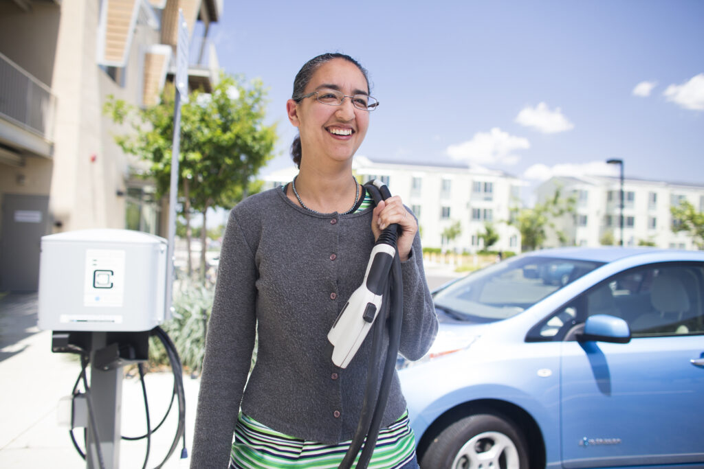 Woman standing in front of her electric car